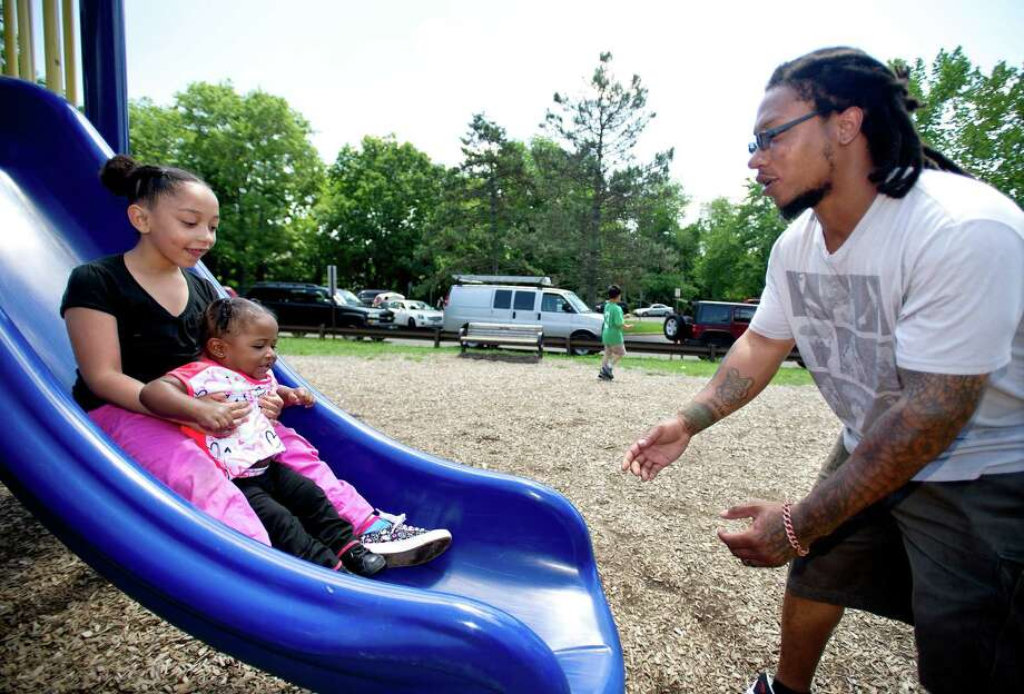 James Clark plays with his daughters, Hylee, 6, and Semaj, 1, at the park at Springdale Elementary School on Saturday, June 15, 2013. Photo: Lindsay Perry / Stamford Advocate