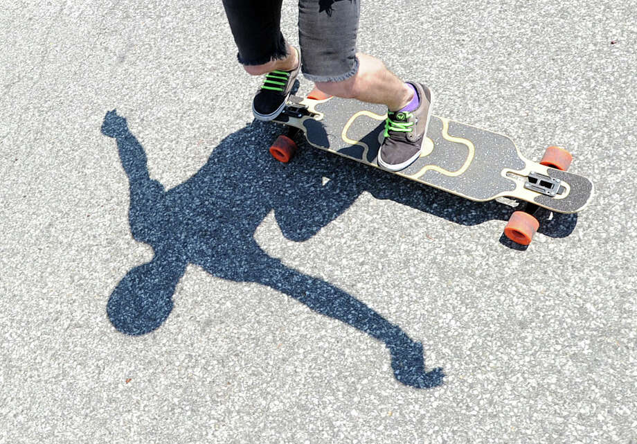 Gary Enright, 21, of Port Chester, N.Y., casts a shadow while giving a skating demonstration on his longboard during the 'Go Skate Festival' celebrating the 10-year anniversary of the Skateboarding Park in Greenwich, Saturday, June 15, 2013. Photo: Bob Luckey / Greenwich Time