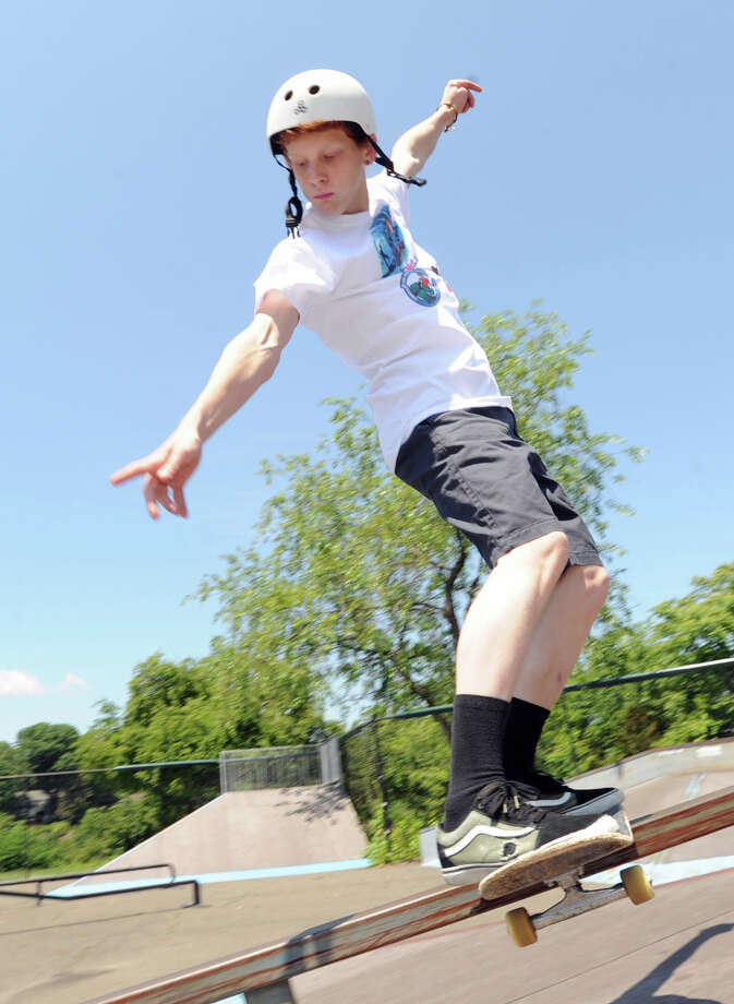 Skateboarder Lucas Perez, 15, of Cos Cob, slides down a metal rail during the 'Go Skate Festival' celebrating the 10-year anniversary of the Skateboarding Park, Greenwich, Saturday, June 15, 2013. Photo: Bob Luckey / Greenwich Time