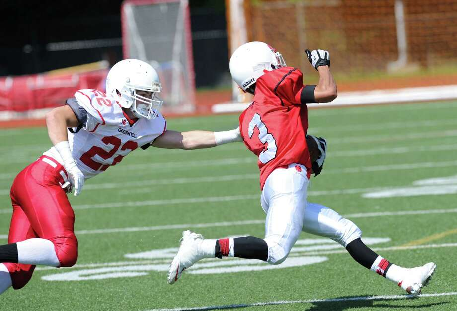 At right, Austin Longi (# 3) of Red gets past the out-stretched arm of Brechan Allison (# 22) of White during the Greenwich High School Red/White football game at the school, Saturday morning, June 15, 2013. Longi scored on the 40-yard running play that was a sweep. Red won the game, 14-0. Photo: Bob Luckey / Greenwich Time