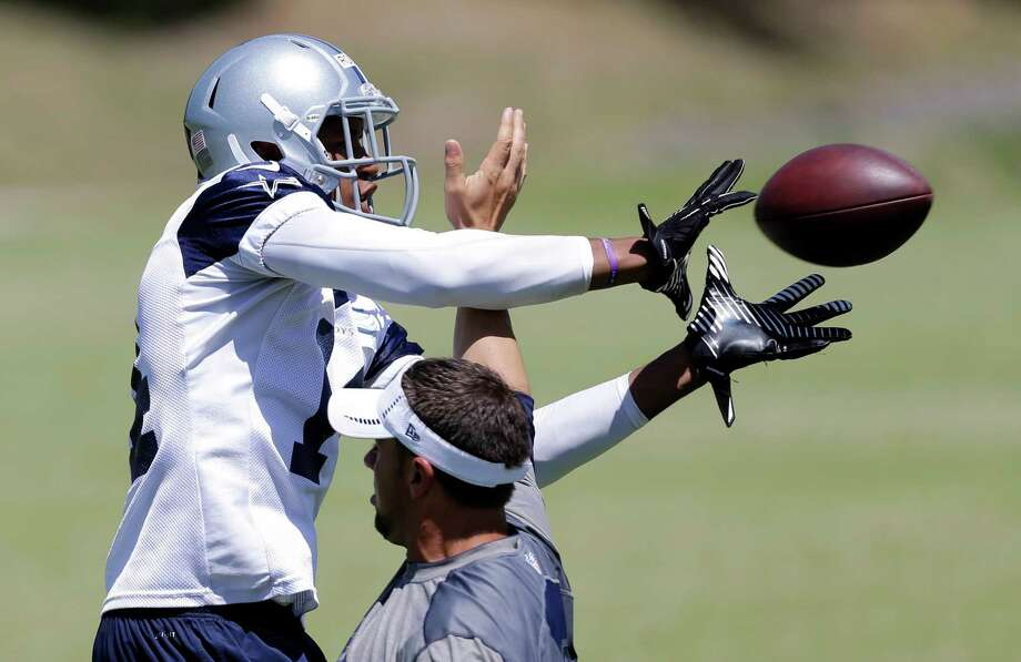 Dallas Cowboys wide receiver Eric Rogers, left, reaches out to grab a pass as offensive quality control coach Keith O'Quinn defends during their NFL football minicamp on Thursday, June 13, 2013, in Irving, Texas. (AP Photo/Tony Gutierrez) Photo: Tony Gutierrez, Associated Press / AP