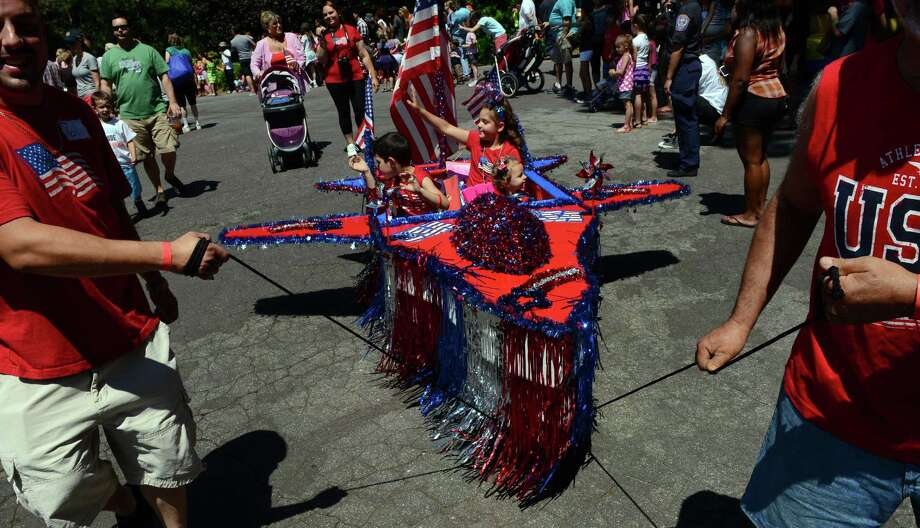 The Barnum Festival's Wing Ding Parade makes its way through Beardsley Zoo in Bridgeport, Conn. on Saturday June 15, 2013. This float is entitled: American Pride in the Sky, and is pulled by proud dad Michael Aquiar, left, and grandfather Michael Fletcher, right. In the float is Mariella Aguiar, 7, waving, brother Michael, 5, and driving is baby sister Lilliana, 15 months. Photo: Christian Abraham / Connecticut Post