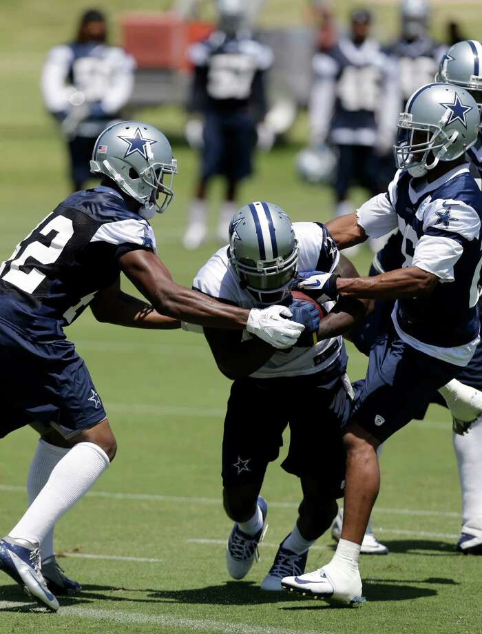 Dallas Cowboys safety Barry Church (42) and safety Will Allen, right, try to strip the ball from wide receiver Dez Bryant as Bryant fights to get into the end zone during NFL football minicamp on Thursday, June 13, 2013, in Irving, Texas. (AP Photo/Tony Gutierrez) Photo: Tony Gutierrez, Associated Press / AP