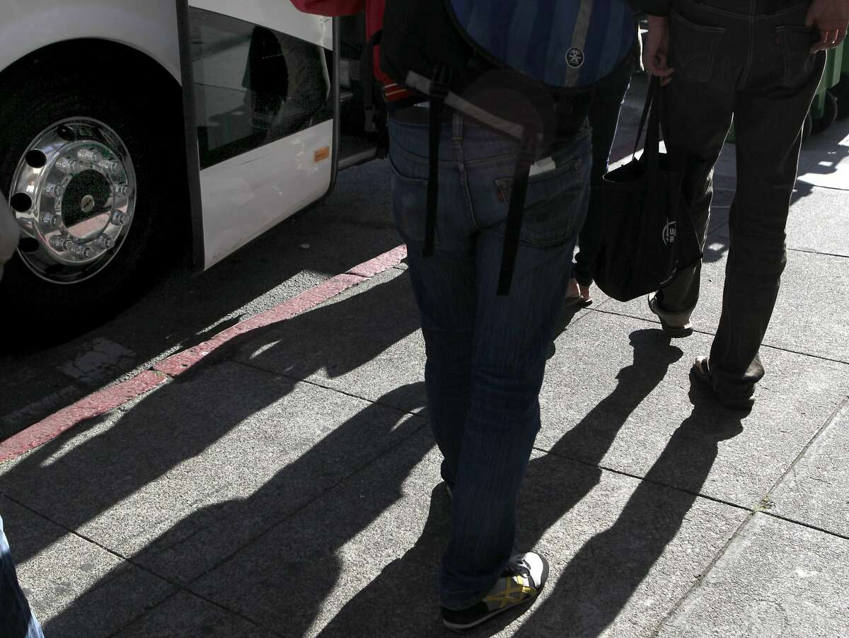 Google employees board a private shuttle bus at 18th and Dolores streets in San Francisco, Calif. that will transport them to Silicon Valley on Friday, June 14, 2013.