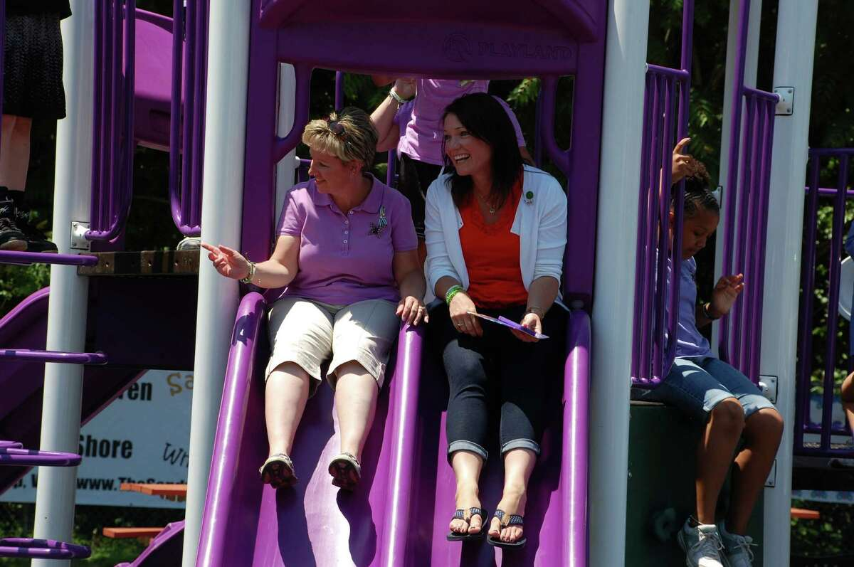 Amy Deloughy of Sandy Hook, left, takes a slide with her neighbor Nicole Hockley, mother of Dylan Hockley, the shooting victim in whose memory the new playground at Long Lots School is dedicated. WESTPORT NEWS, CT 6/15/13