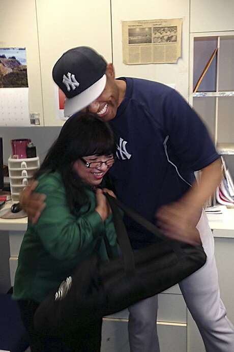 Mariano Rivera hugs Julie Vasconcellos, an A's mailroom employee for 25 years, after surprising her before New York's game in Oakland. Photo: Janie McCauley, Associated Press