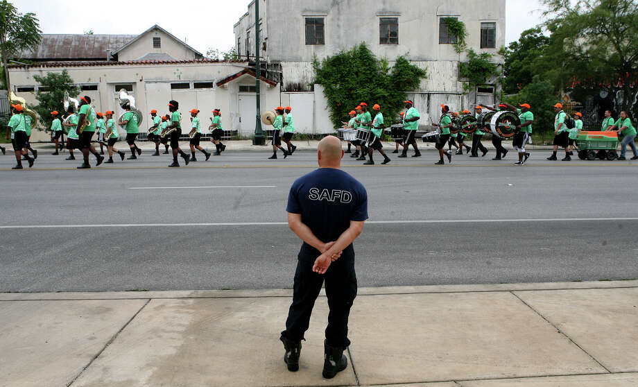 Paul Watts, with the San Antonio Fire Department,  watches the Sam Houston High School band June 15, 2013 as the 15th Annual Juneteenth Freedom Parade passes Firestation #3 on East Commerce Street. The parade is put on by the Juneteenth Freedom Coalition. Photo: Cynthia Esparza, For San Antonio Express-News / For San Antonio Express-News