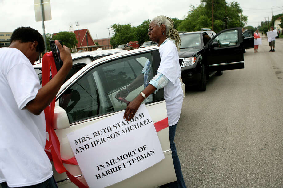 Beverly Harris attaches signs to the cars that were participating in the 15th Annual Juneteenth Freedom Parade June 15, 2013. The parade,  put on by the Juneteenth Freedom Coalition, began at the intersection of Cherry and East Commerce Street. Photo: Cynthia Esparza, For San Antonio Express-News / For San Antonio Express-News
