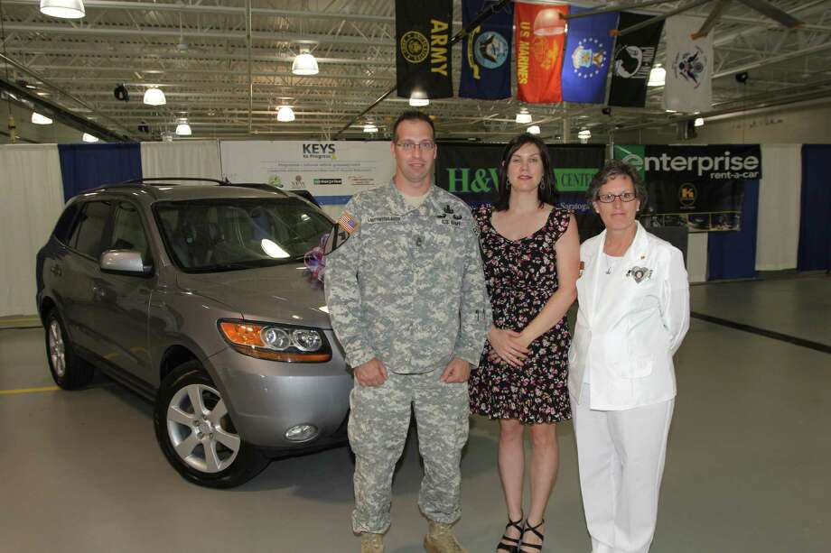 Tom Killips Master Sgt. Eric Lautenschlager, his wife, Lacey, and Carrie Farley, Albany Chapter 11 of the Gold Star Mothers president, show the rebuilt 2007 Hyundai Santa Fe. / All Rights Reserved