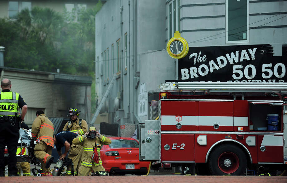 Firefighters from Terrell Hills and Alamo Heights Fire Departments work a fire at the Broadway 50-50 on Broadway in Alamo Heights. Northbound traffic on Broadway was closed for several hours due to the smoldering fire. Photo: Joe Cavaretta / JOE CAVARETTA