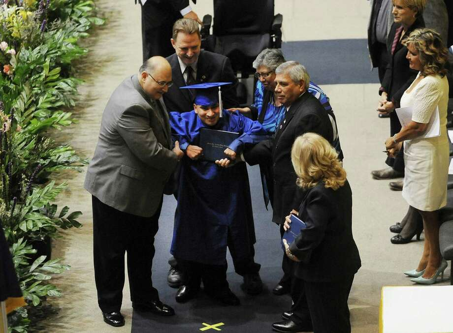 Jesse Martinez receives his diploma during the graduation for South San at Freeman Coliseum on Saturday, June 15, 2013. Jesse was born with cerebral palsy and lost his legs shortly after birth. Usually confined to a wheelchair, he walked across the stage on prosthetics and with help. Photo: Billy Calzada, San Antonio Express-News / San Antonio Express-News