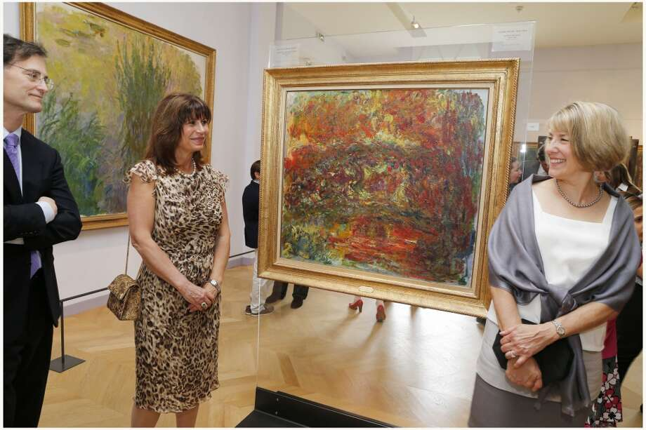 Dr. Gary and Cathy Brock, and Margaret Parker standing beside a Monet