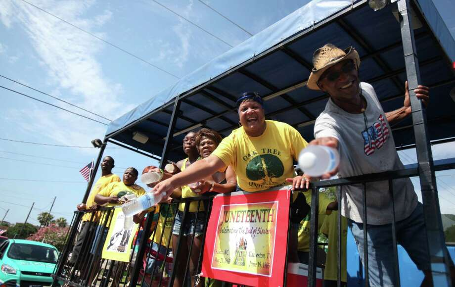 Juneteenth parade participants cheer and hand out water during the hot morning of the Galveston Juneteenth Parade on Saturday, June 15, 2013, in Houston. Photo: Mayra Beltran / © 2013 Houston Chronicle
