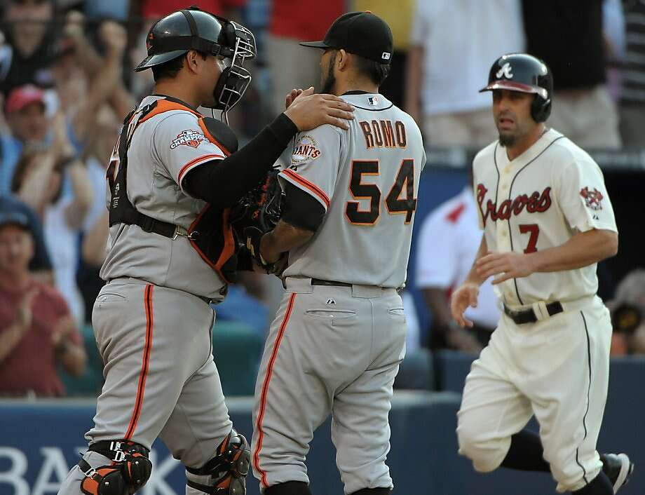 San Francisco Giants pitcher Sergio Romo (54) huddles with catcher Guillermo Quiroz after walking in Atlanta Braves' Reed Johnson for the tying run during the ninth inning of their baseball game at Turner Field, Saturday, June 15, 2013, in Atlanta. The Braves won 6-5. (AP Photo/David Tulis) Photo: Dave Tulis, Associated Press