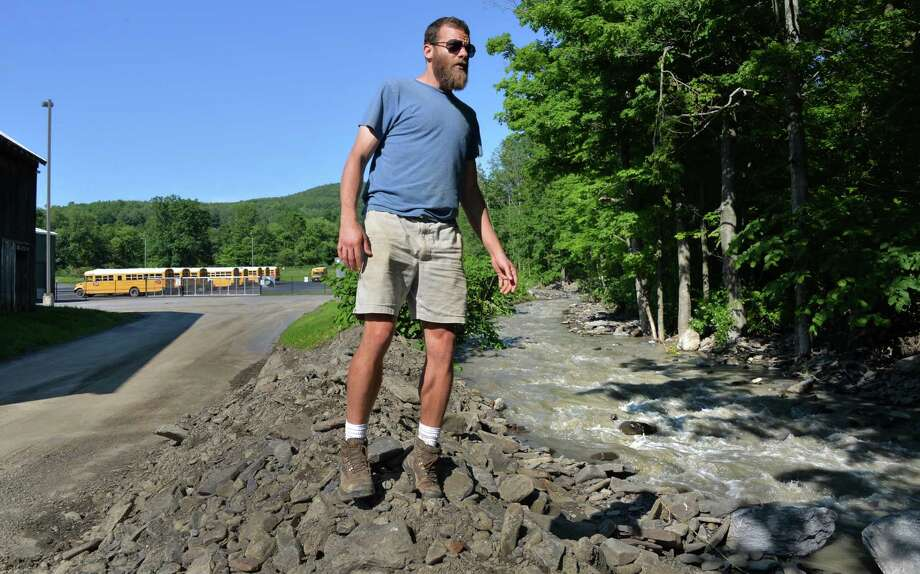 Travis Durfee of Montour Falls, looks over the flooded creek that damages his brothers home Saturday June 15, 2013, following yesterday's flashflood that swept down Main Street in Middleburgh, NY.   (John Carl D'Annibale / Times Union) Photo: John Carl D'Annibale / 10022833A