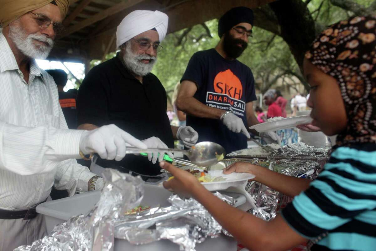 Members of the Sikh Dharam Sal serve food at the World Refugee Day celebration at St. Francis Episcopal Church in San Antonio on Saturday, June 15, 2013.