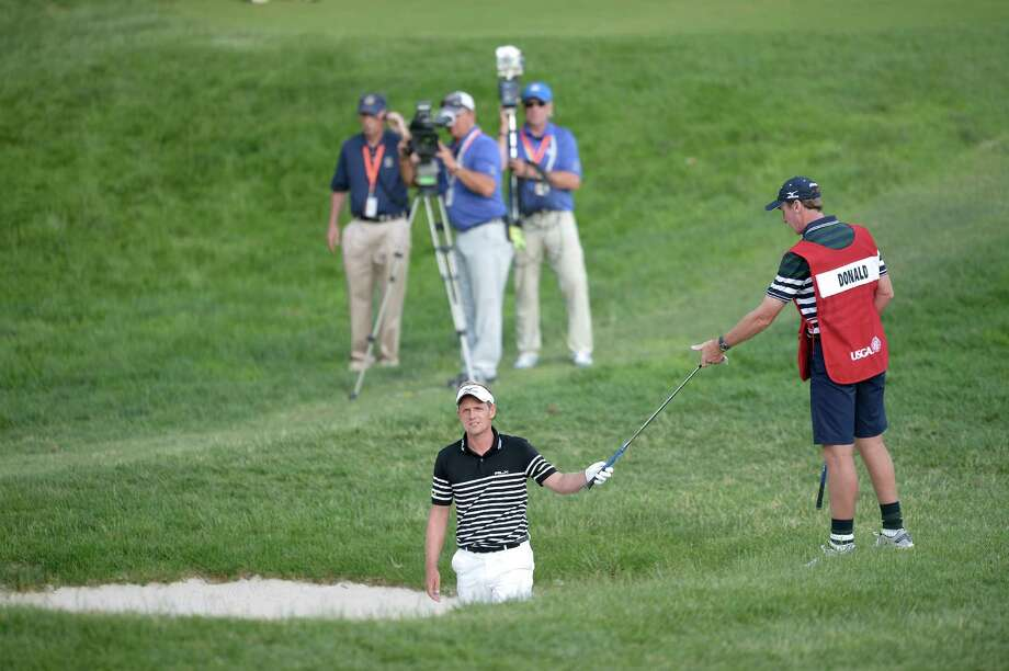Luke Donald of England is handed a club before hitting out of a sand trap on the 17th hole during the third round of the US Open at Merion Golf Club June 15, 2013 in Ardmore, Pennsylvania. AFP PHOTO/Brendan SMIALOWSKIBRENDAN SMIALOWSKI/AFP/Getty Images Photo: BRENDAN SMIALOWSKI, AFP/Getty Images / Brendan SMIALOWSKI