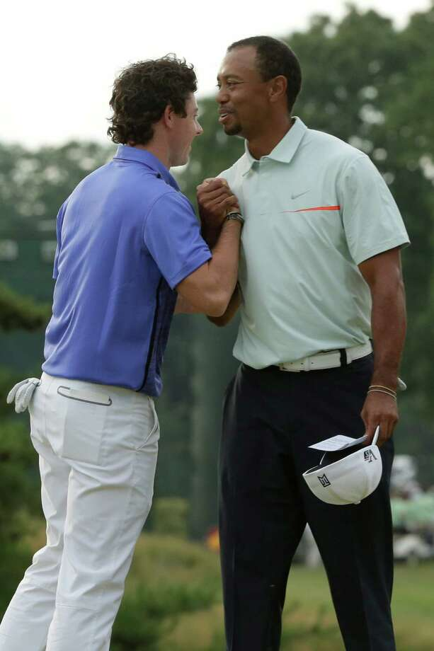 Tiger Woods, right, and Rory McIlroy, of Northern Ireland, greet after putting on the 18th hole during the third round of the U.S. Open golf tournament at Merion Golf Club, Saturday, June 15, 2013, in Ardmore, Pa. (AP Photo/Charlie Riedel) Photo: Charlie Riedel, Associated Press / AP