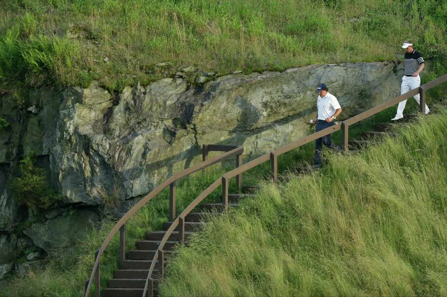 Phil Mickelson, left, and Luke Donald, of England, walk down from the 17th tee box during the third round of the U.S. Open golf tournament at Merion Golf Club, Saturday, June 15, 2013, in Ardmore, Pa. (AP Photo/Julio Cortez) Photo: Julio Cortez, Associated Press / AP