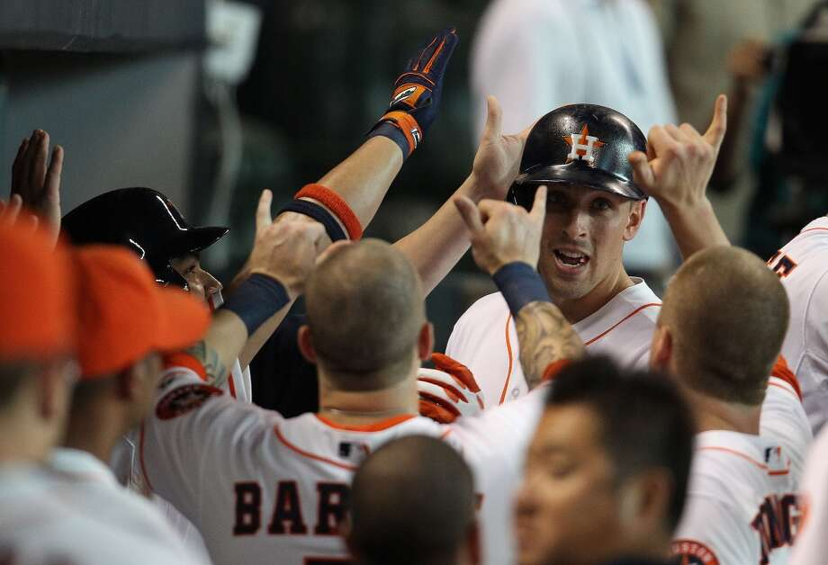 Astros catcher Jason Castro reacts with teammates in the dugout after his home run.