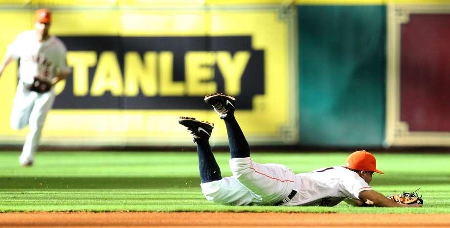 Astros second baseman Jose Altuve dives for a single hit by White Sox shortstop Alexei Ramirez.