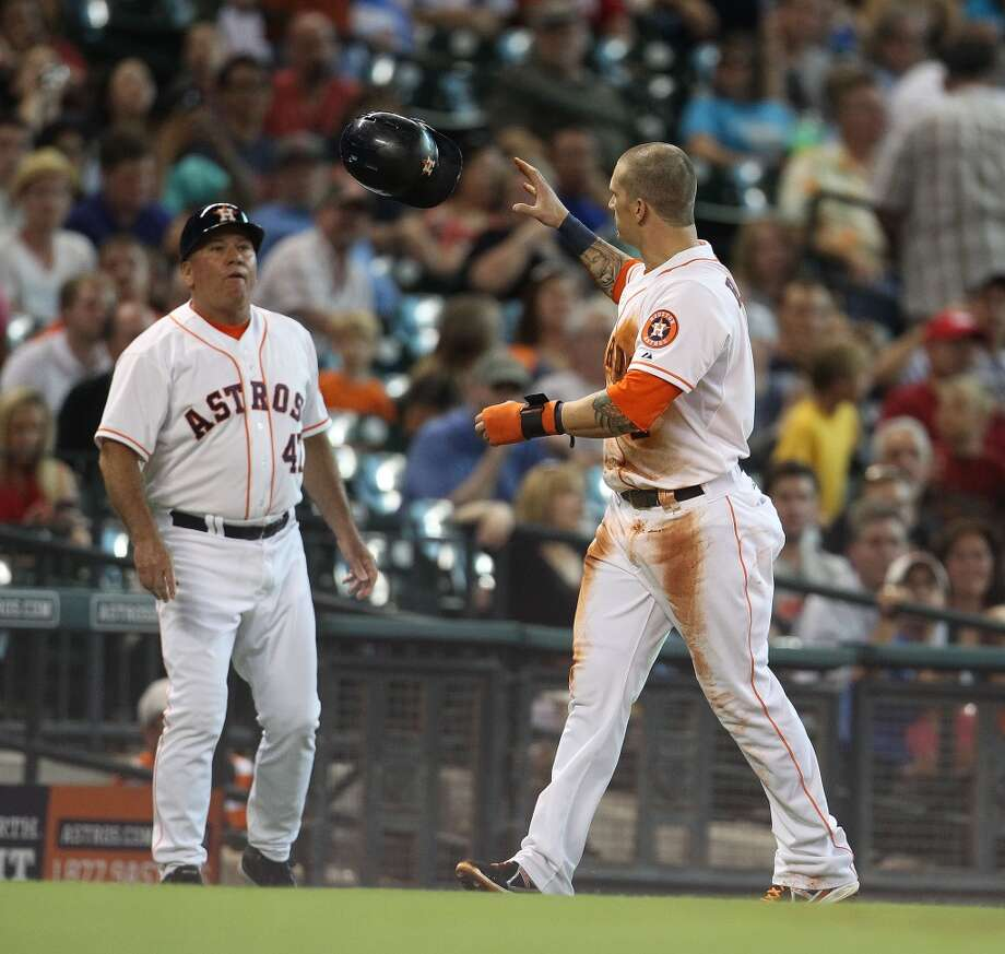 Astros third base coach Dave Trembley  tosses a batting helmet back to Astros center fielder Brandon Barnes.