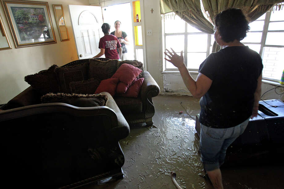 Alicia Vargas walks through the mess of her family home while Gabriella Gallegos greets another family member Lupita Cardenas at the front door during cleanup in the aftermath of flooding in Eagle Pass.  on  June 16, 2013. Photo: TOM REEL