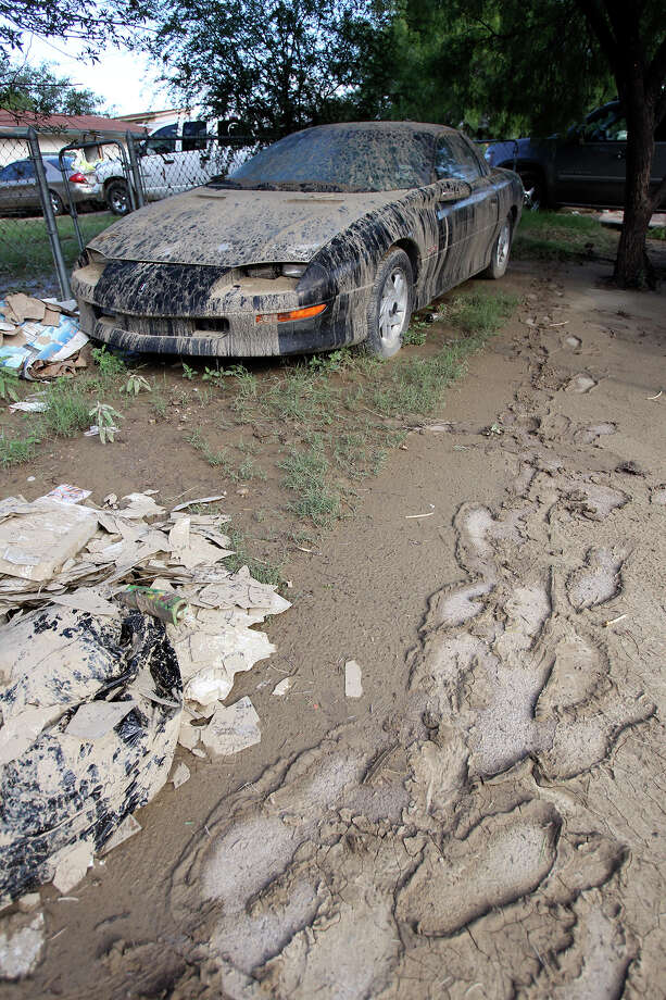 A car which was totally submerged is one of several destroyed on Barrera street as cleanup in the aftermath of flooding in Eagle Pass continues..  on  June 16, 2013. Photo: TOM REEL