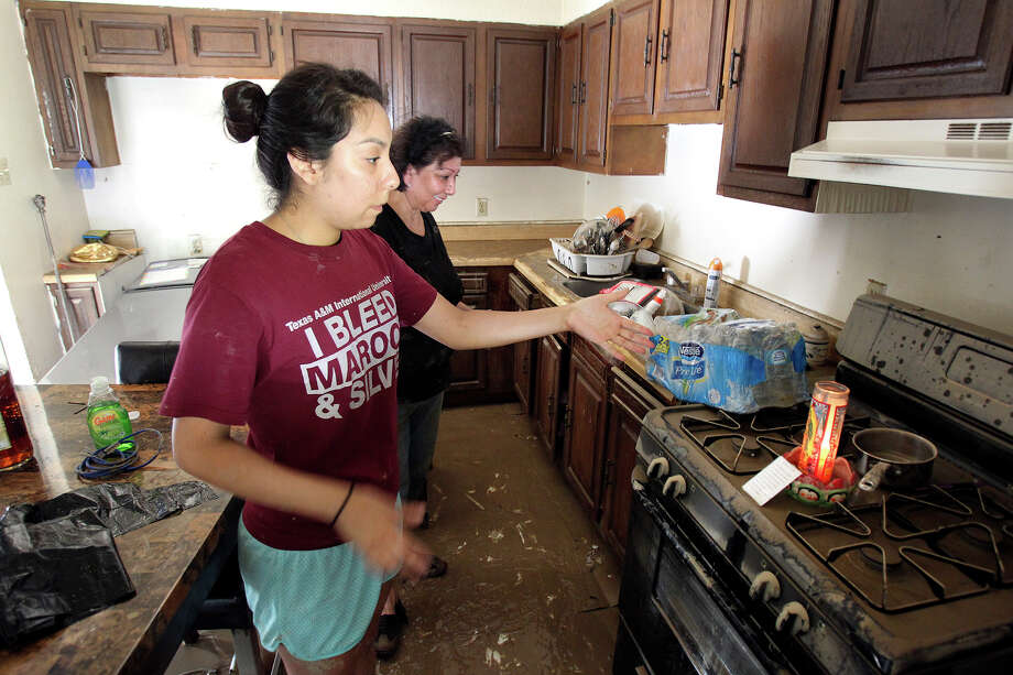 Gabriella Gallegos describes the candle which kept burning in her family home even as the entire house was folded with water as the cleanup in the aftermath of flooding in Eagle Pass continues.  on  June 16, 2013. Photo: TOM REEL