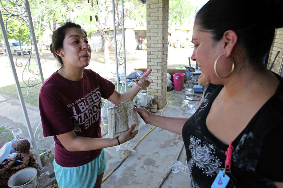Gabriella Gallegos offers an emotional description of a booklet given to her as Lupita Cardenas listens during explains cleanup in the aftermath of flooding in Eagle Pass.  on  June 16, 2013. Photo: TOM REEL