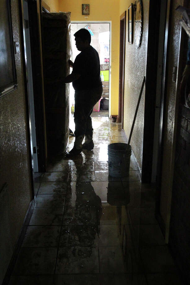 Jesus Vargas pulls a mattress from a bedroom in the home of a relative during cleanup in the aftermath of flooding in Eagle Pass.  on  June 16, 2013. Photo: Express-News File Photo