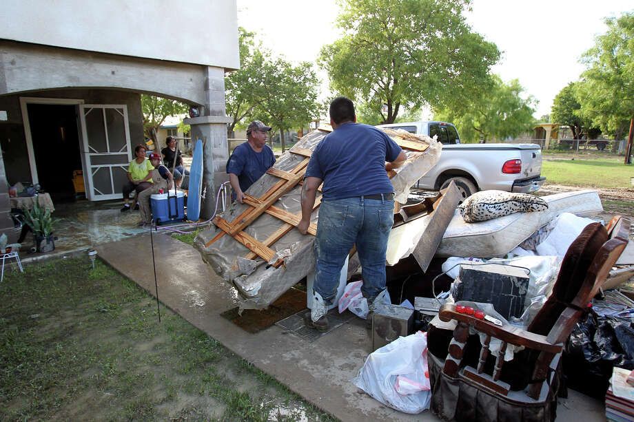 Fortino Vargas (left) and Jesus Vargas throw a ruined mattress on the trash pile near Barrera street during cleanup in the aftermath of flooding in Eagle Pass.  on  June 16, 2013. Photo: TOM REEL