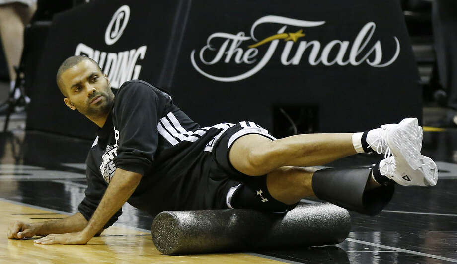 Spurs point guard Tony Parker uses a foam roller to stretch out during practice Saturday at the AT&T Center.