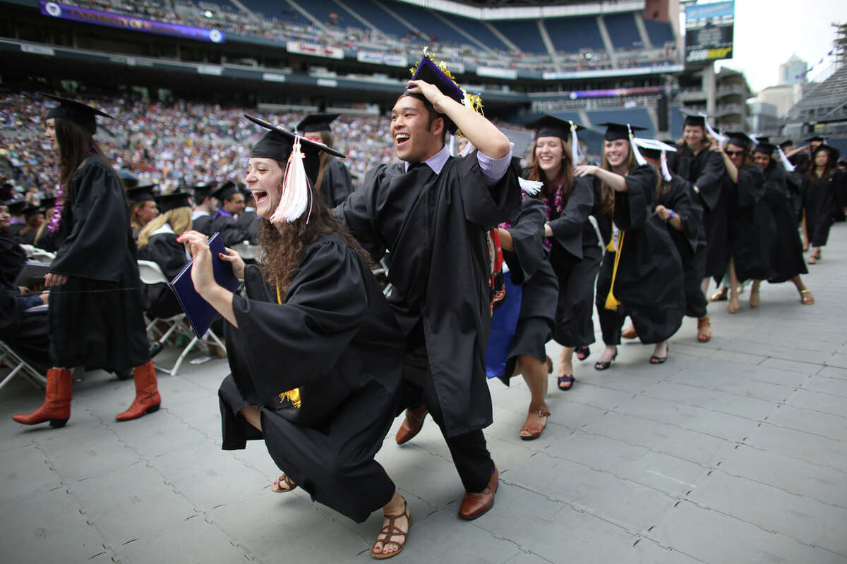 Graduates just awarded degrees form a conga line as they make their way back to their seats during the University of Washington's 2013 commencement ceremony at CenturyLink Field in Seattle on Saturday, June 15, 2013. Students were ceremonially awarded bachelors, masters and doctorate degrees during the ceremony.