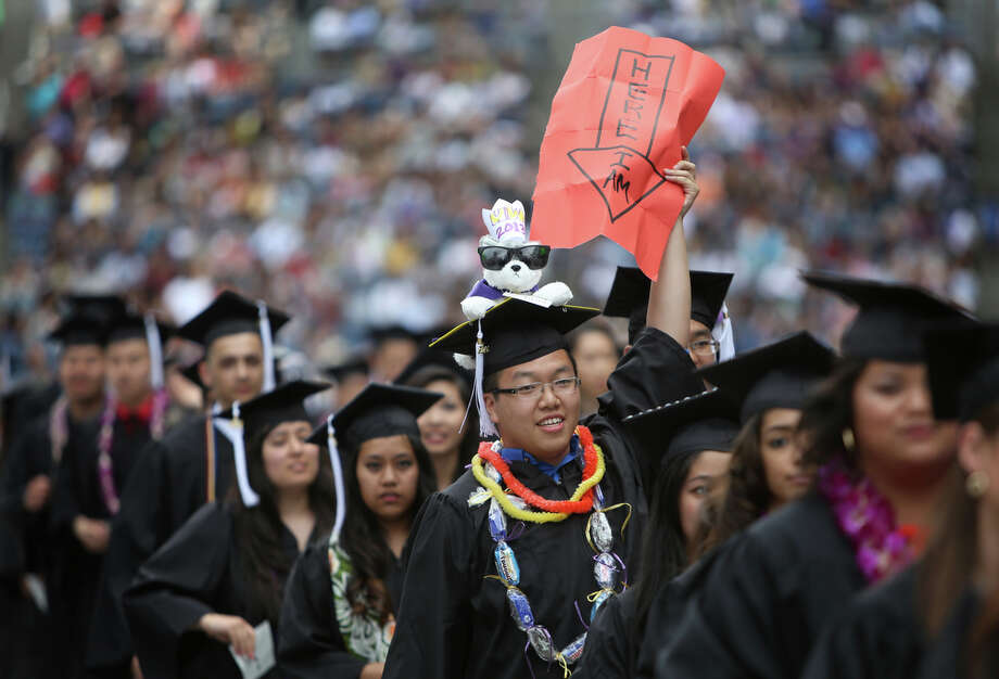 Vincent Kwan lets his family and friends know where he is in the sea of graduates. Photo: JOSHUA TRUJILLO, SEATTLEPI.COM / SEATTLEPI.COM