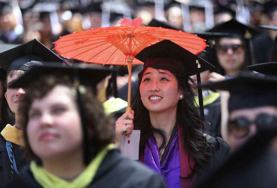 A graduate seeks shelter from the sun. Photo: JOSHUA TRUJILLO, SEATTLEPI.COM / SEATTLEPI.COM
