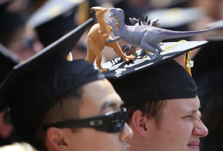 Plastic dinosaurs seem to be fighting on a graduate's mortar board. Photo: JOSHUA TRUJILLO, SEATTLEPI.COM / SEATTLEPI.COM