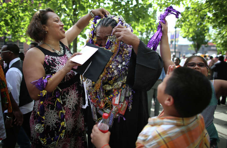 Graduate Toalei Mulitauaopele is covered with candy and money leis by his sister, Maomi Mulitauaopele. Photo: JOSHUA TRUJILLO, SEATTLEPI.COM / SEATTLEPI.COM