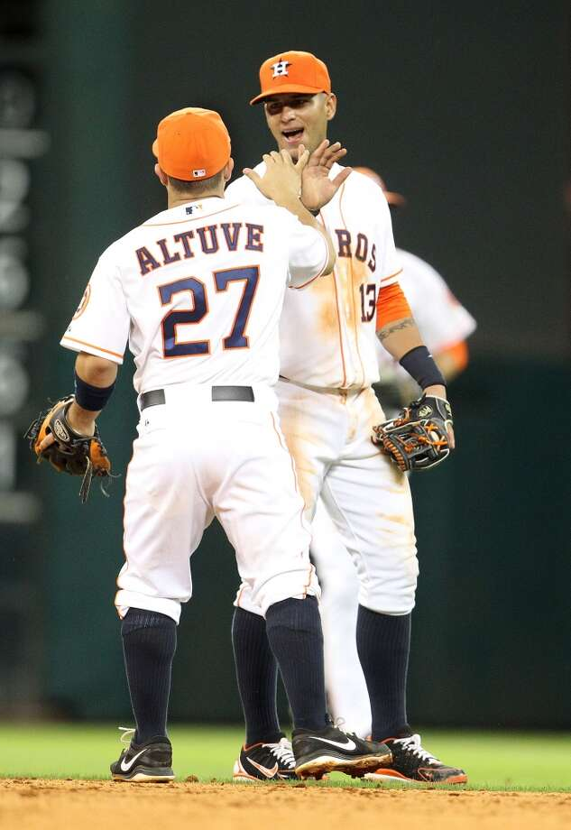 Astros shortstop Ronny Cedeno and second baseman Jose Altuve celebrate Jordan Danks was picked off at second to end the game.