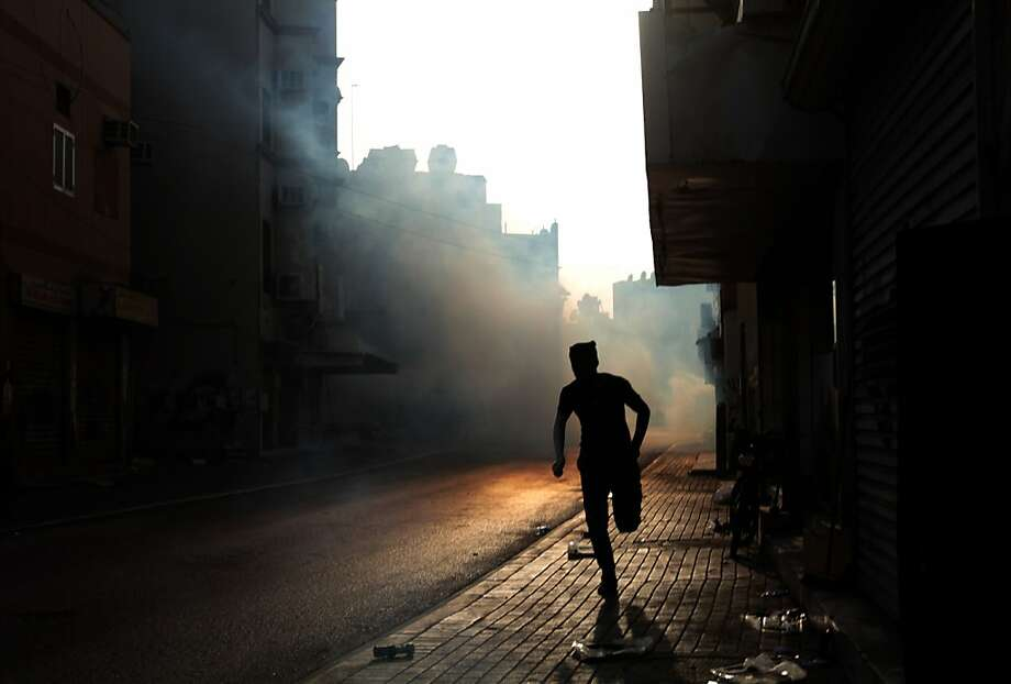 A Bahraini anti-government protester reacts to tear gas fired by riot police during clashes in Bilad al-Qadeem village, Bahrain, on Saturday, June 15, 2013. Days after the government announced it had arrested key members of the February 14 group, the group called on Bahrainis to sit outside their houses in a show of defiance and to hold rallies Saturday, prompting clashes with riot police in villages throughout the Gulf island kingdom. (AP Photo/Hasan Jamali) Photo: Hasan Jamali, Associated Press