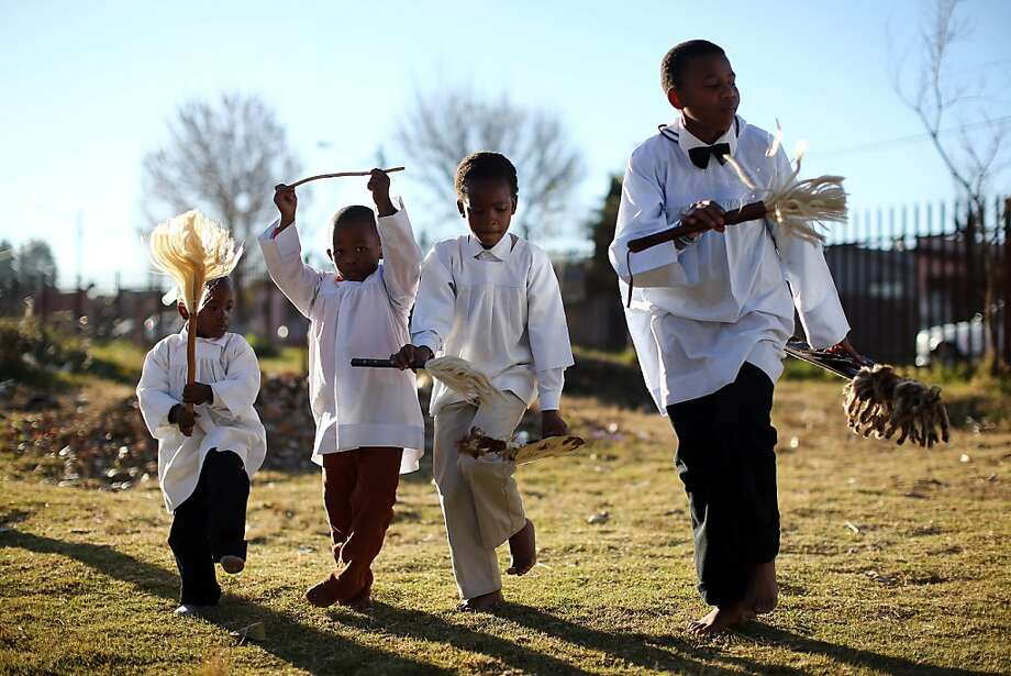 JOHANNESBERG, SOUTH AFRICA - JUNE 15:  Children try to keep up with elders as members of the Church of Nazareth take part in a service at Rockville School, in Soweto on June 15, 2013 in Johannesburg, South Africa. The Baptist church, which is a mixture of Zulu tradition and Christianity, continued their daily life as the former South African President and leader of the anti-apartheid movement who is spending a seventh night in hospital. It has been reported that he is responding better to treatment for a recurring lung infection.  (Photo by Dan Kitwood/Getty Images)  Photo: Dan Kitwood, Getty Images