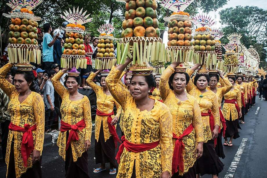 DENPASAR, BALI, INDONESIA - JUNE 15:  Women wearing costumes carry fruit offerings on their heads during a parade for the opening of the Bali International Art Festival on June 15, 2013 in Denpasar, Bali, Indonesia. The annual month-long festival runs from June 15 to July 13, 2013 and features 340 local and international art communities with thousands of performers.  (Photo by Putu Sayoga/Getty Images)  Photo: Putu Sayoga, Getty Images