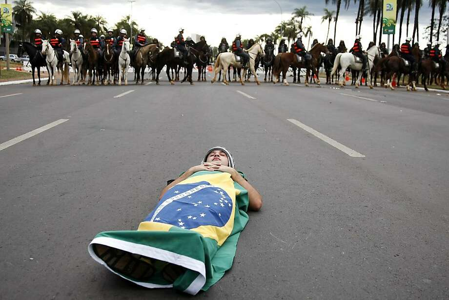 A demonstrator lies on the street wrapped with a Brazilian flag during a rally near Brasilia's Estadio Nacional Mane Garrincha to protest against the allocation of funds towards the Confederations Cup and next year's World Cup at a time when Brazil is in dire need of investment in other areas, they argue on June 15, 2013, prior opening Confederation match between Brazil and Japan. AFP PHOTO/Beto BARATA.BETO BARATA/AFP/Getty Images Photo: Beto Barata, AFP/Getty Images
