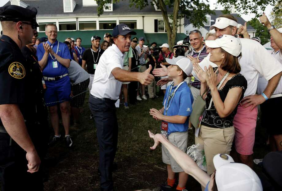 U.S. Open leader Phil Mickelson connects with the gallery at Merion Golf Club in Ardmore, Pa., as he heads to the scorer's tent after completing the third round. Photo: Rob Carr, Staff / 2013 Getty Images