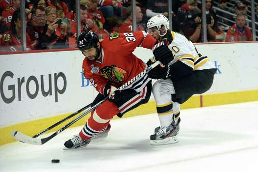CHICAGO, IL - JUNE 15:  Michal Rozsival #32 of the Chicago Blackhawks attempts to control the puck against Daniel Paille #20 of the Boston Bruins in Game Two of the NHL 2013 Stanley Cup Final at United Center on June 15, 2013 in Chicago, Illinois. Photo: Harry How, Getty Images / 2013 Getty Images
