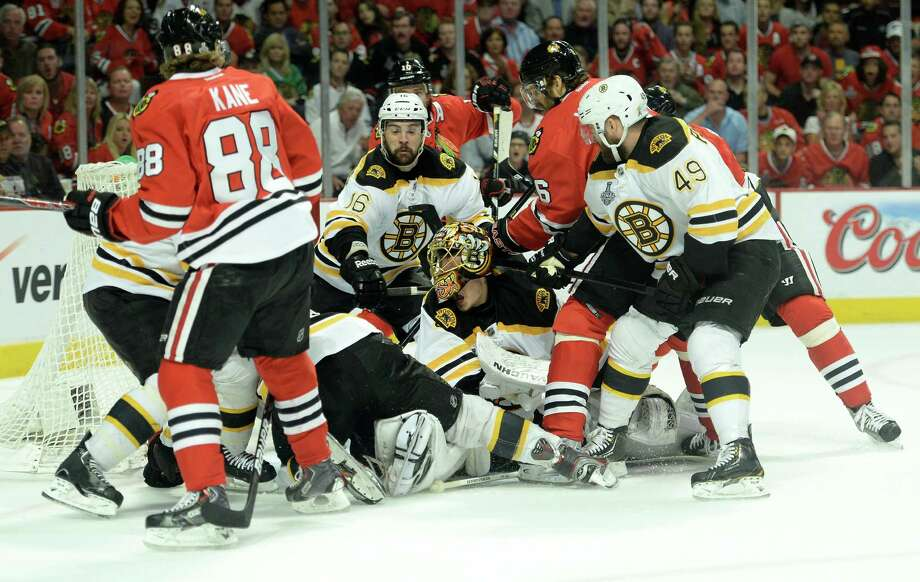 CHICAGO, IL - JUNE 15:  Goalie Tuukka Rask #40 of the Boston Bruins has his helmet knocked off as players surround the net against the Chicago Blackhawks in Game Two of the NHL 2013 Stanley Cup Final at United Center on June 15, 2013 in Chicago, Illinois. Photo: Harry How, Getty Images / 2013 Getty Images