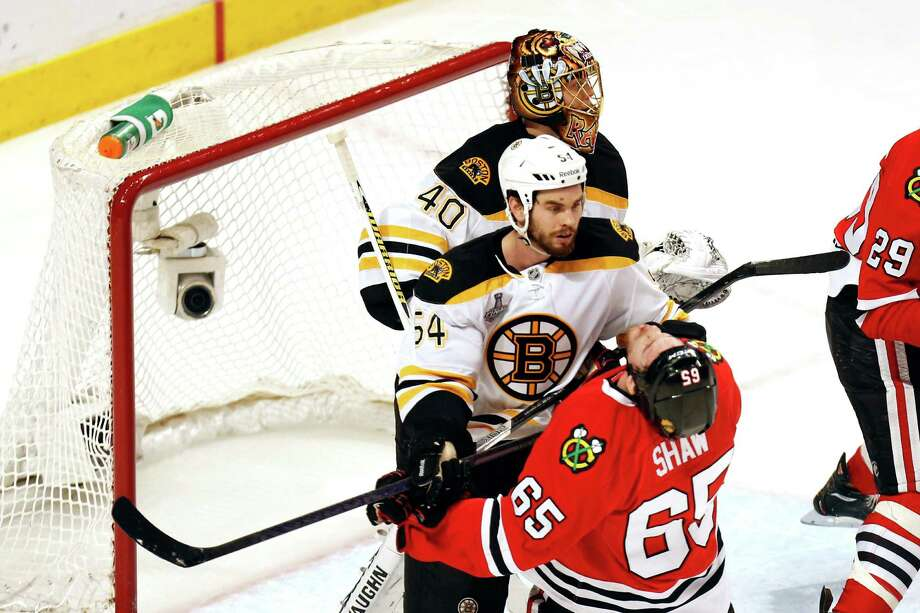 CHICAGO, IL - JUNE 15:  Adam McQuaid #54 of the Boston Bruins checks Andrew Shaw #65 of the Chicago Blackhawks in Game Two of the NHL 2013 Stanley Cup Final at United Center on June 15, 2013 in Chicago, Illinois. Photo: Gregory Shamus, Getty Images / 2013 Getty Images