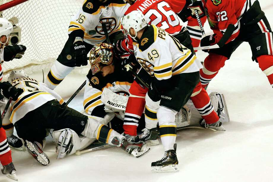 CHICAGO, IL - JUNE 15:  Goalie Tuukka Rask #40 of the Boston Bruins has his helmet knocked off as players surround the net against the Chicago Blackhawks in Game Two of the NHL 2013 Stanley Cup Final at United Center on June 15, 2013 in Chicago, Illinois. Photo: Gregory Shamus, Getty Images / 2013 Getty Images