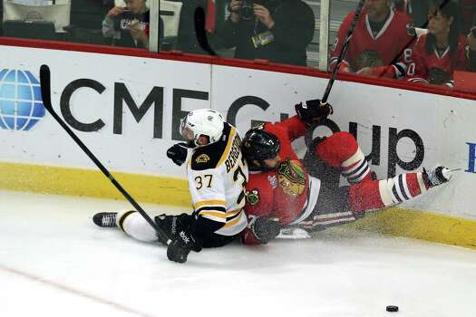 CHICAGO, IL - JUNE 15:  Patrice Bergeron #37 of the Boston Bruins and Brent Seabrook #7 of the Chicago Blackhawks slide down the ice into the boards in Game Two of the NHL 2013 Stanley Cup Final at United Center on June 15, 2013 in Chicago, Illinois. Photo: Jonathan Daniel, Getty Images / 2013 Getty Images