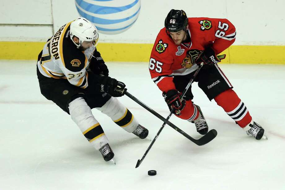 CHICAGO, IL - JUNE 15:  Andrew Shaw #65 of the Chicago Blackhawks attempts to control the puck against Patrice Bergeron #37 of the Boston Bruins in Game Two of the NHL 2013 Stanley Cup Final at United Center on June 15, 2013 in Chicago, Illinois. Photo: Jonathan Daniel, Getty Images / 2013 Getty Images